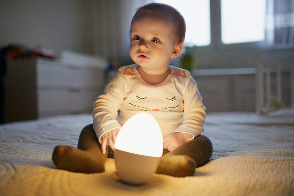 baby reading next to night light