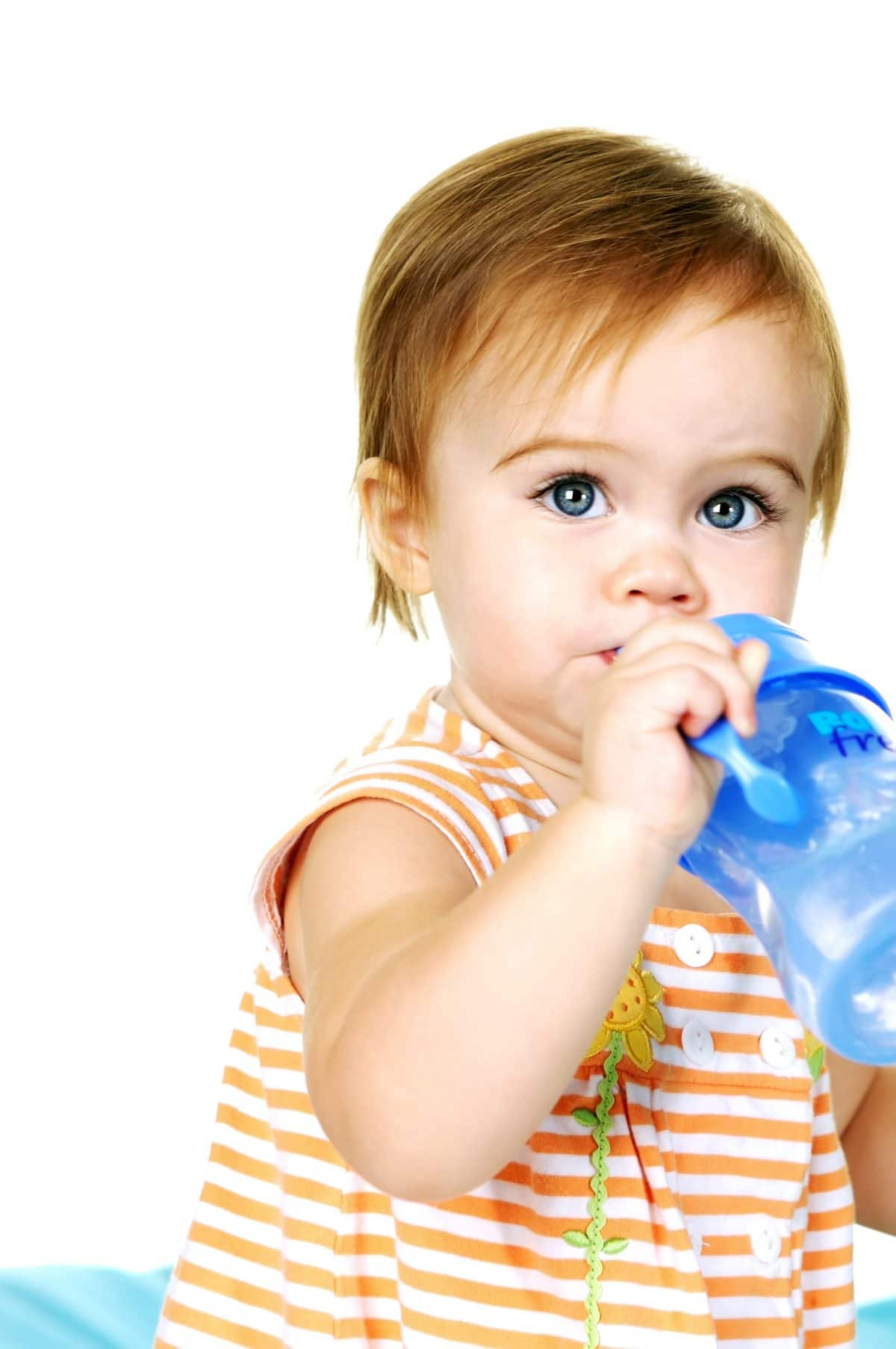 toddler drinking water from a sippy cup