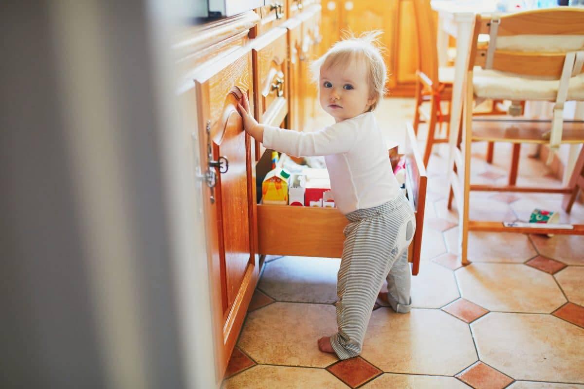 toddler opening kitchen drawer