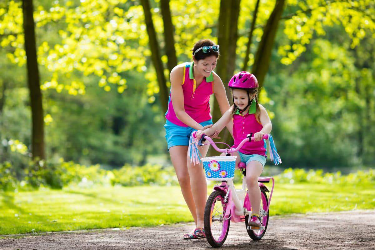 toddler riding a bike with her mom