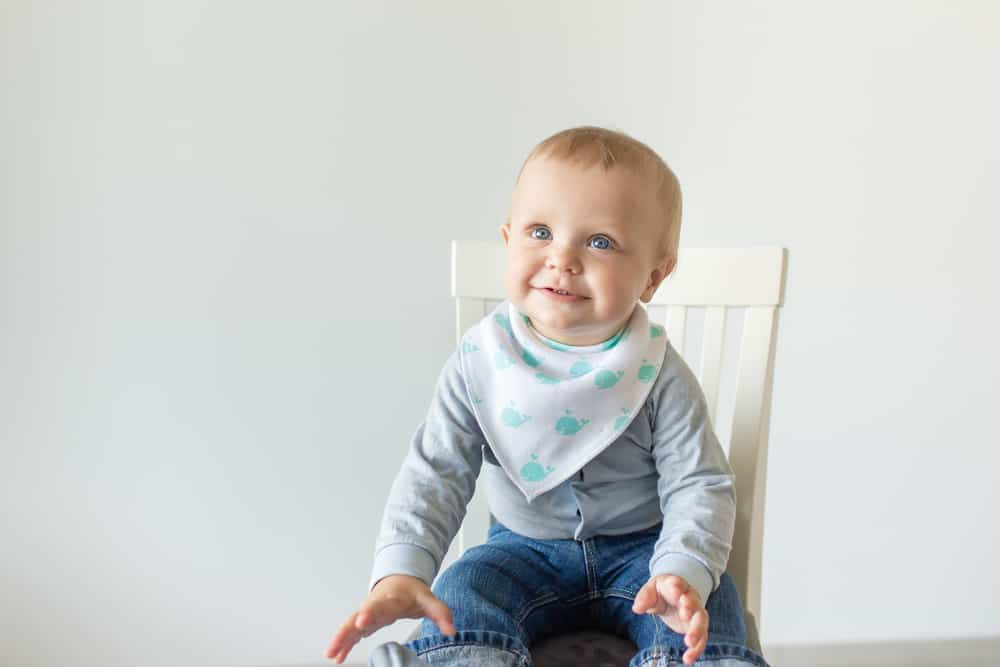 Baby in chair with his arms out, wearing a bib