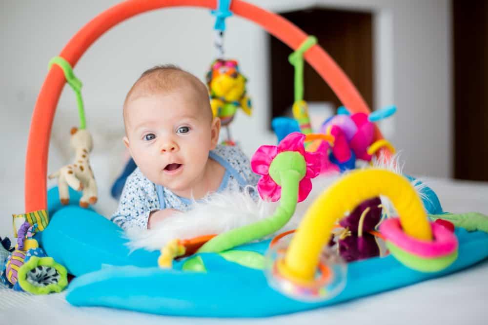 Cute baby boy on colorful gym