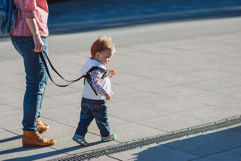 Mother walking with a child on a child leash on a sidewalk