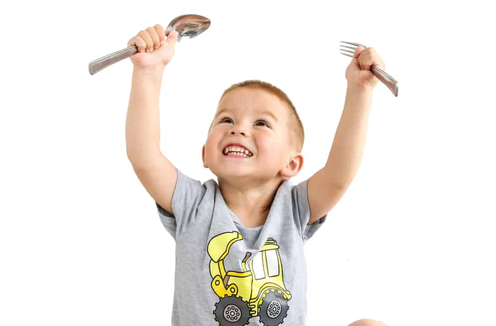 Young boy holding a fork and a spoon