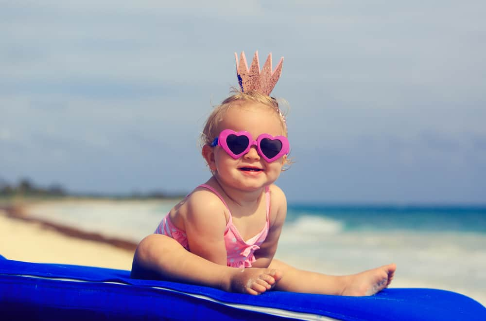 baby girl in a swimsuit and sunglasses on a surfboard