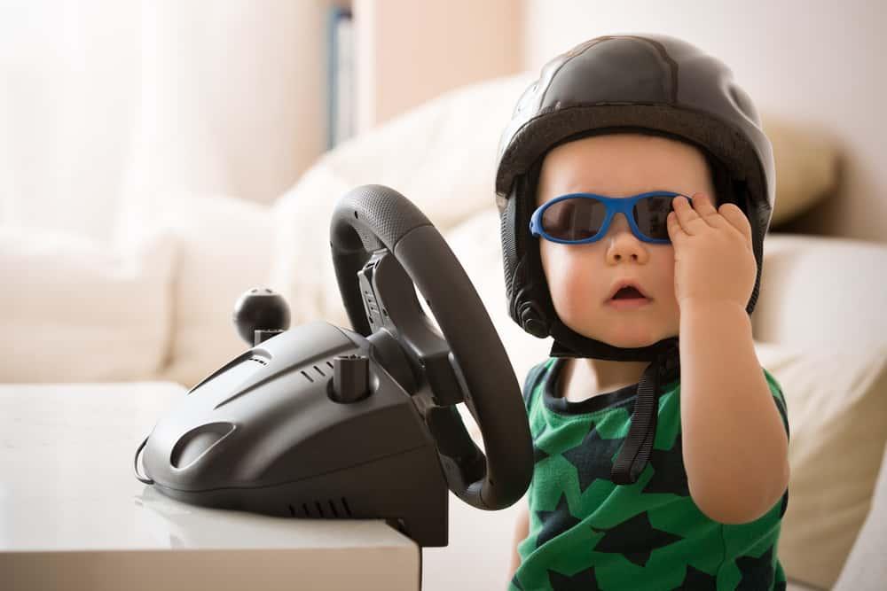 cute bab boy in sunglasses pretending to drive