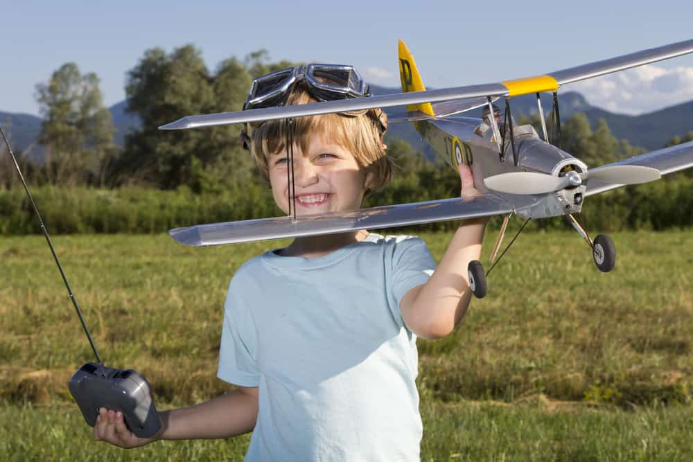 smiling child holding remote control airplane