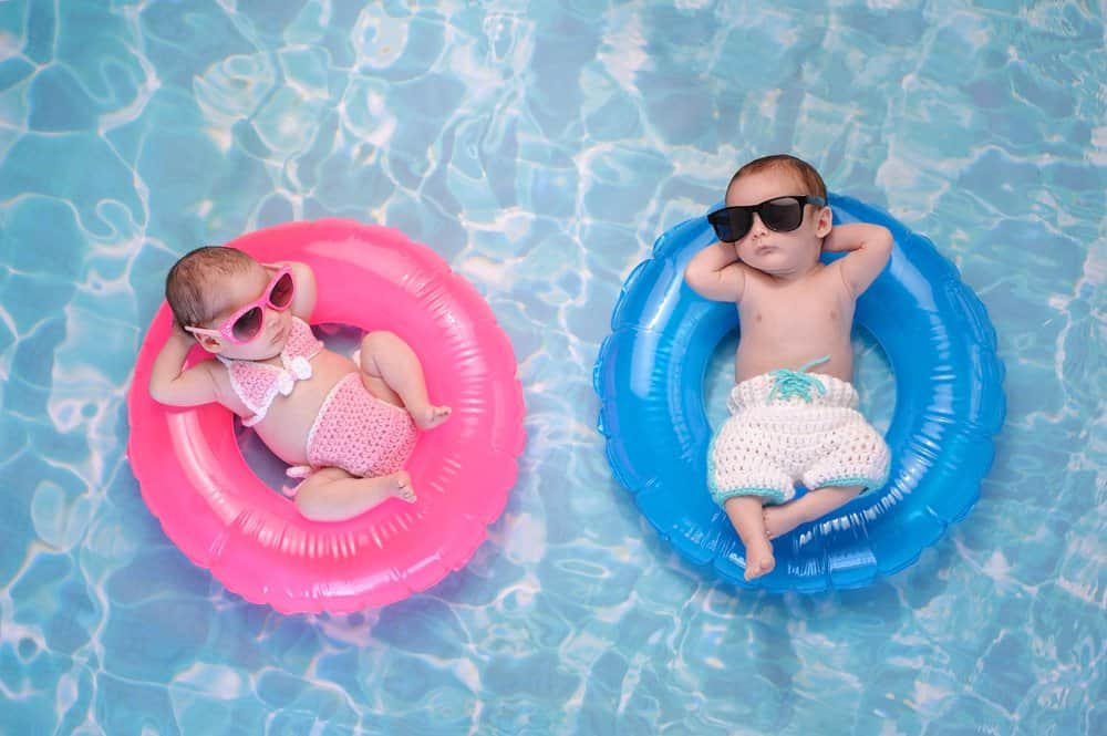 twin babies lounging in a pool with sunglasses on