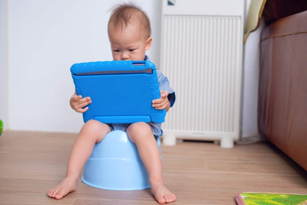 Asian boy on potty watching video on a tablet