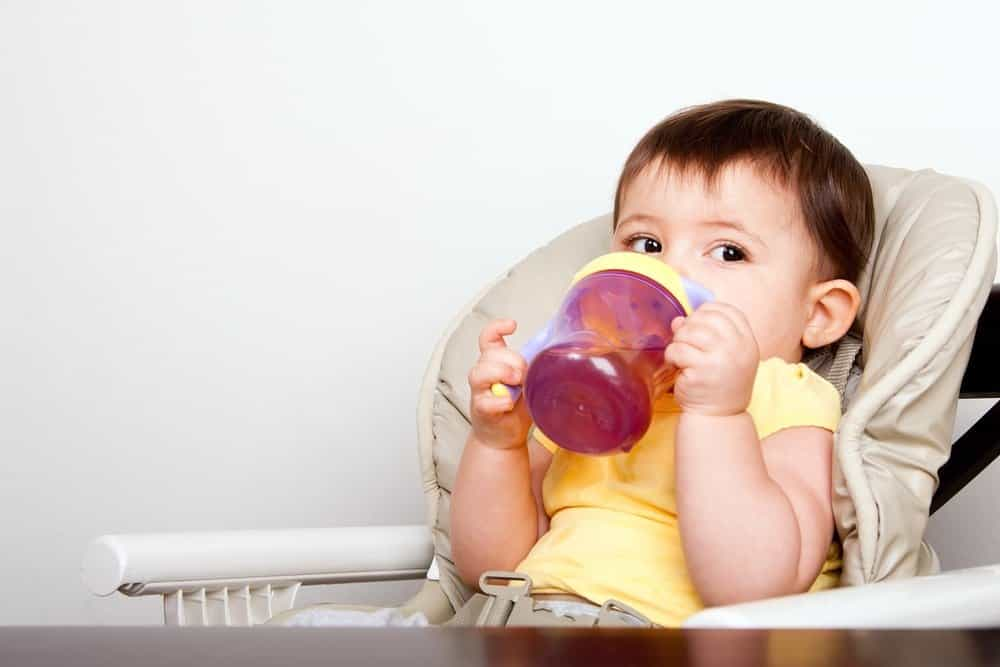 a baby in a high chair drinking out of a sippy cup