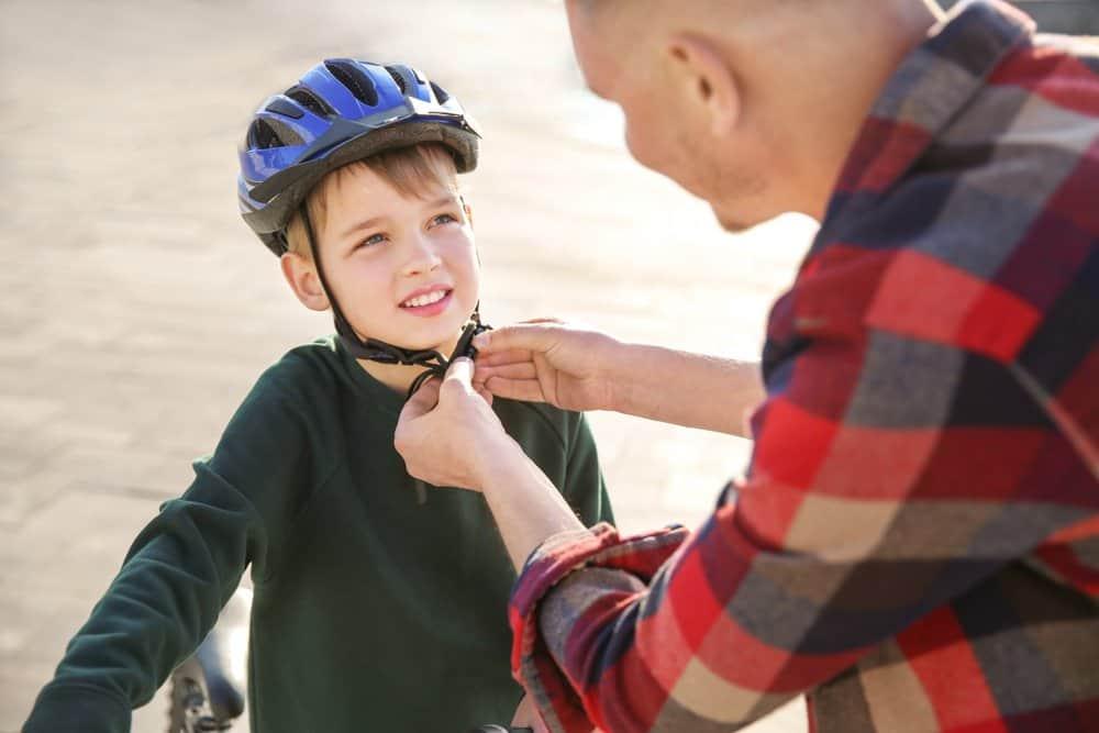 parent helping child put on bike helmet