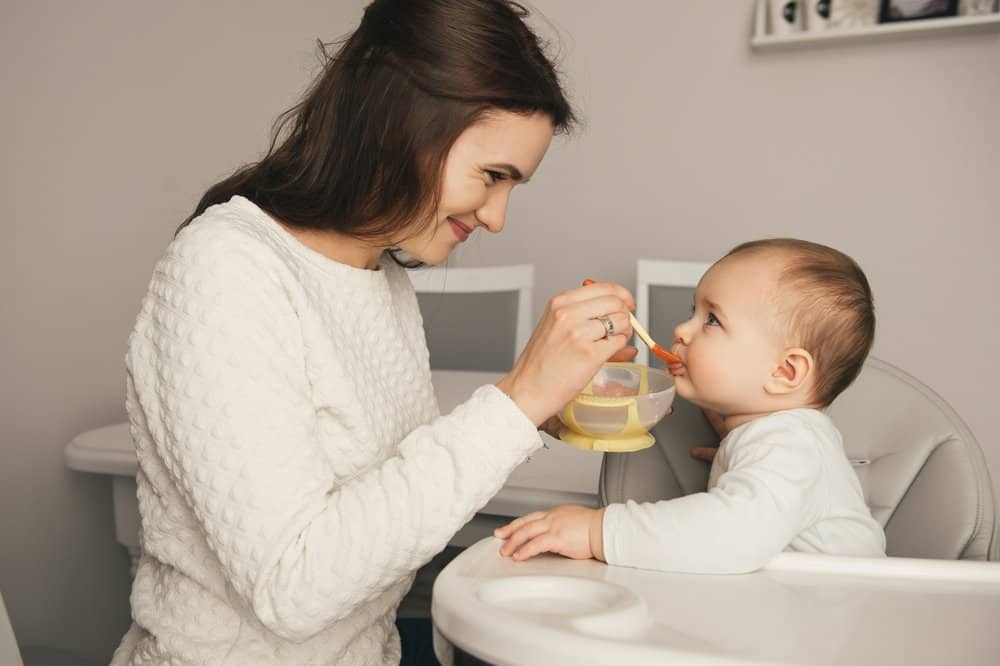 Mother in white sweater feeding her child