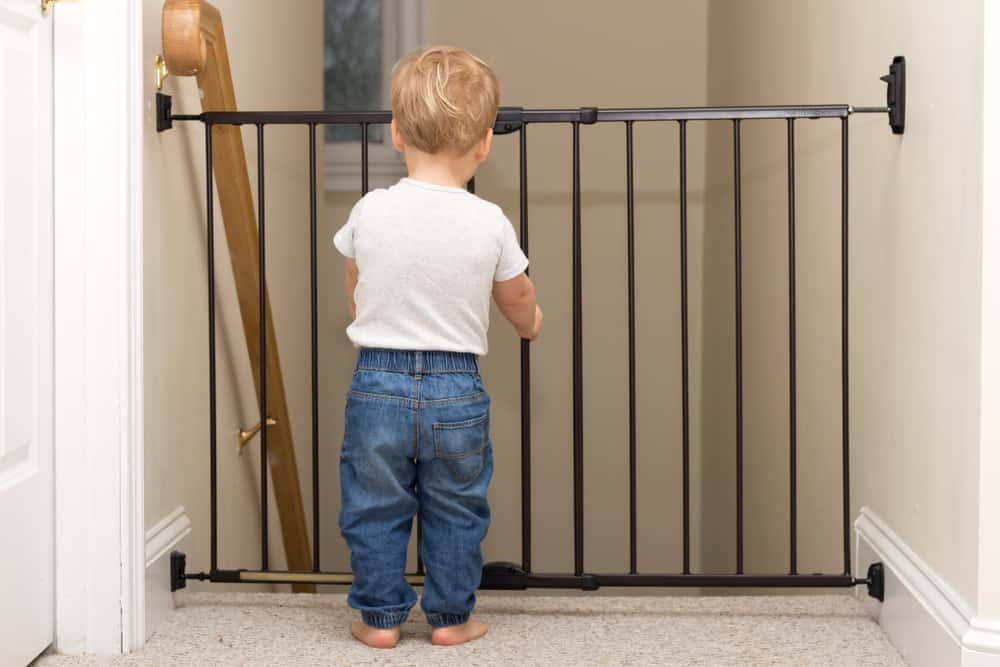 Child standing in front of a baby gate