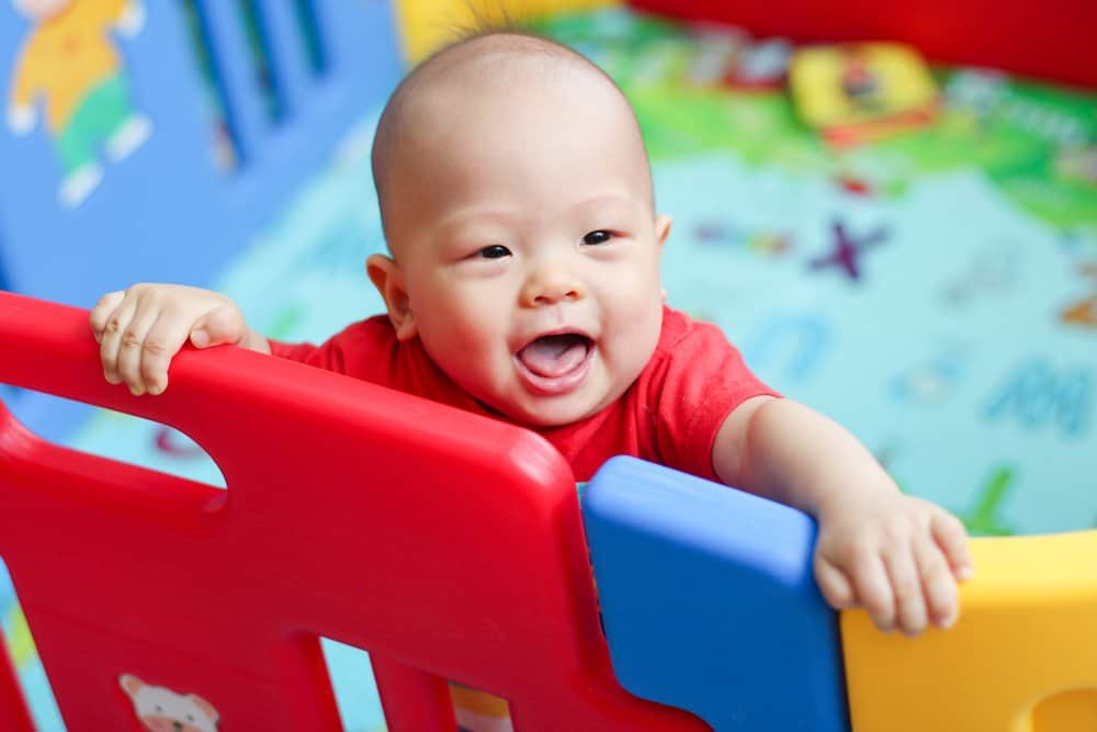 Baby in a red playpen
