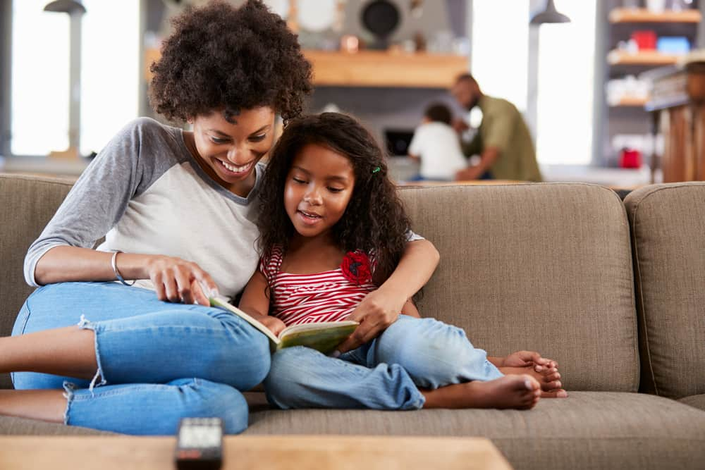 mom and daughter reading on couch