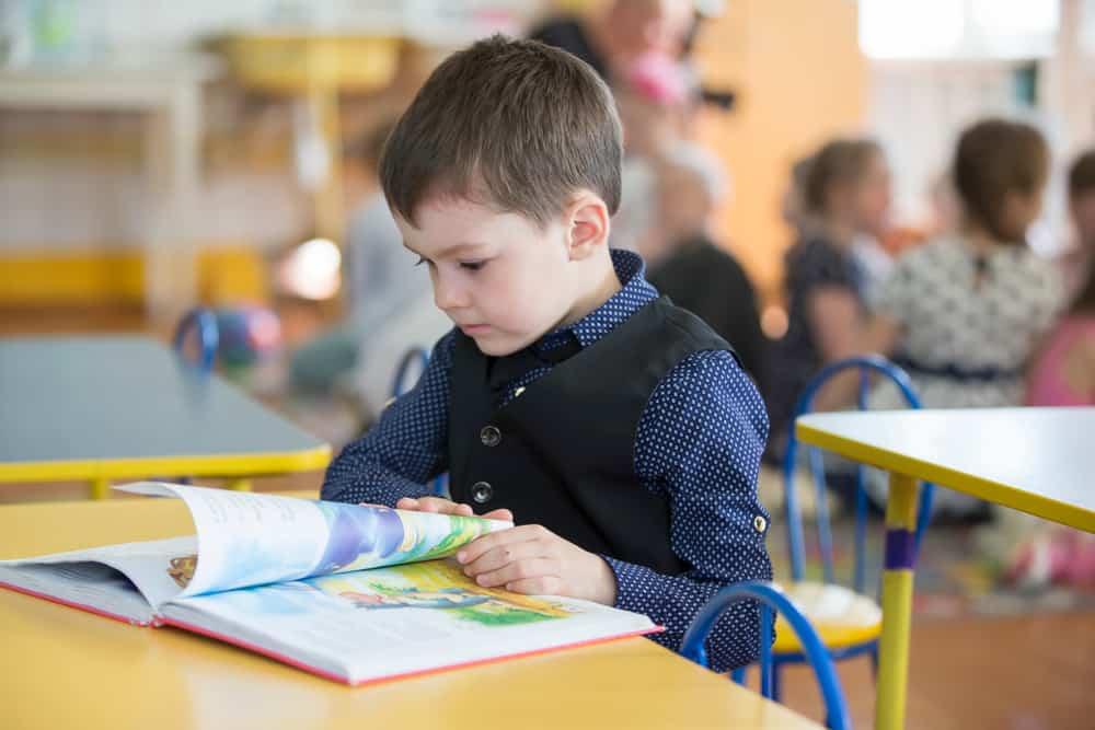 boy exploring book at his desk