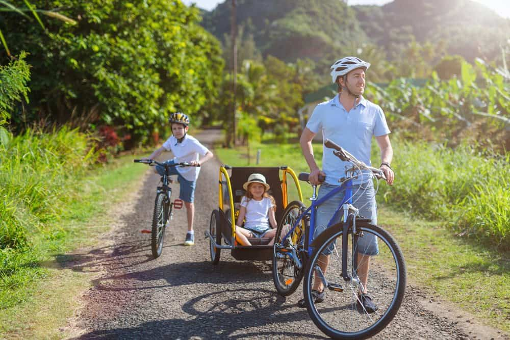 father and children biking through country roads with bike trailer