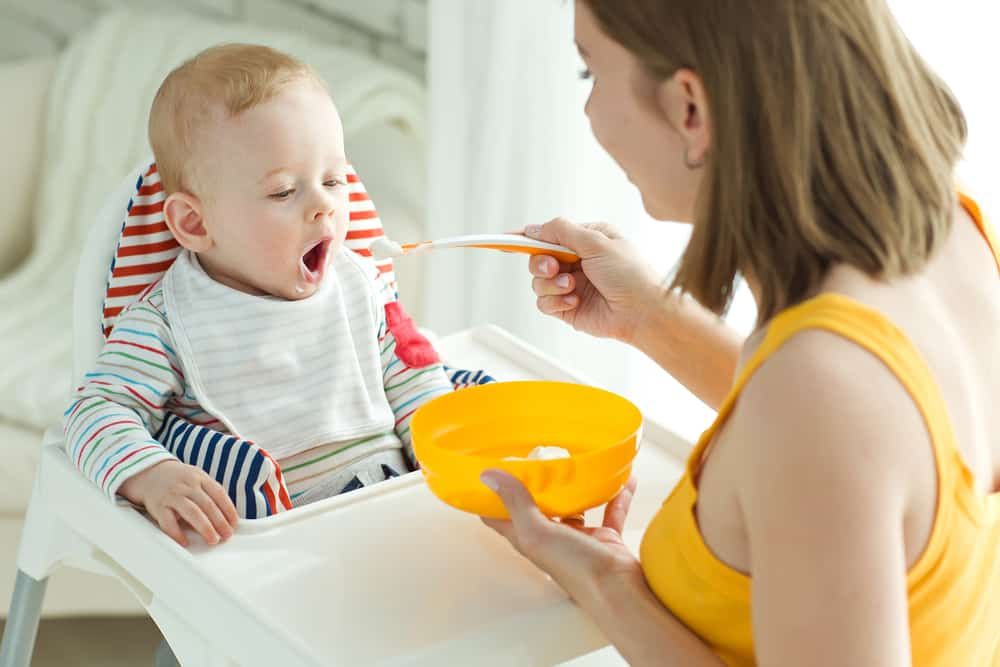 Mother feeding child in a high chair