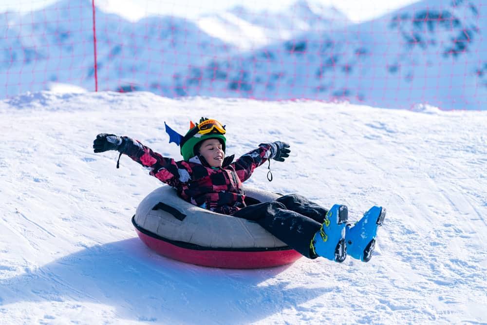 little boy in winter gear sledding on snow tube