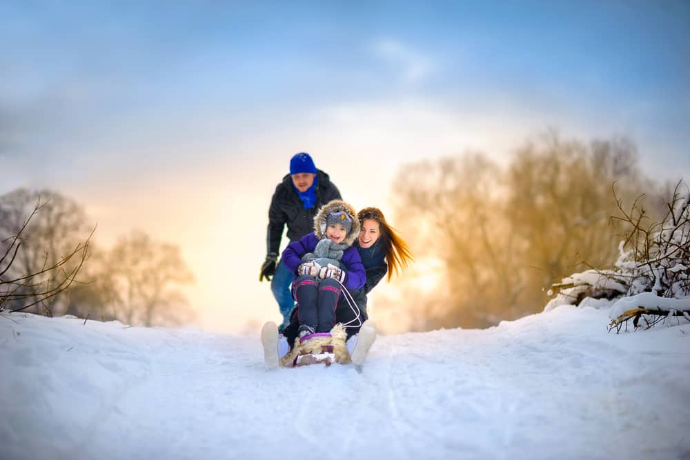 happy husband and wife sledding with their little girl