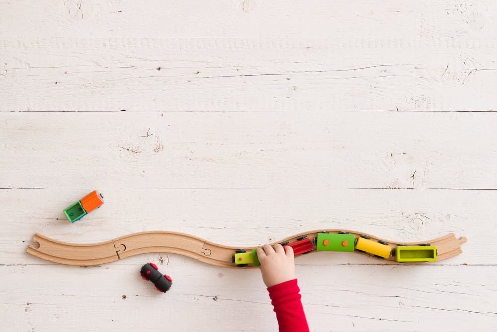 A child's hand playing with wooden trains on wooden train tracks situated on a table