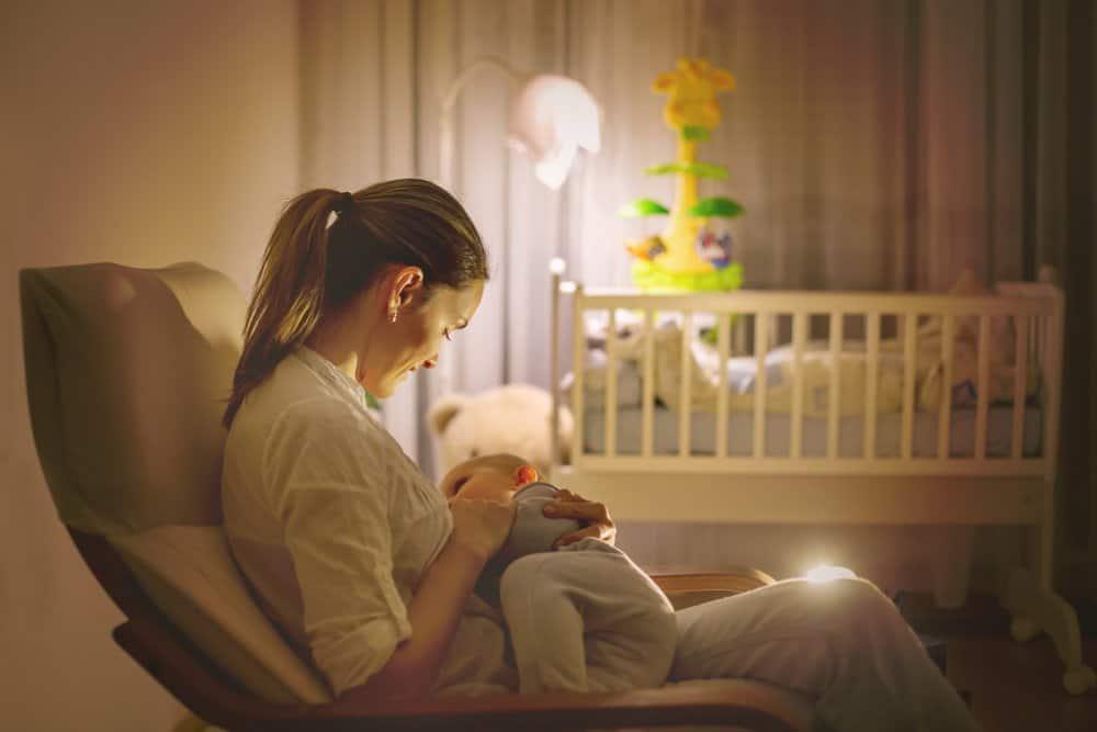 woman breastfeeding baby in nursery