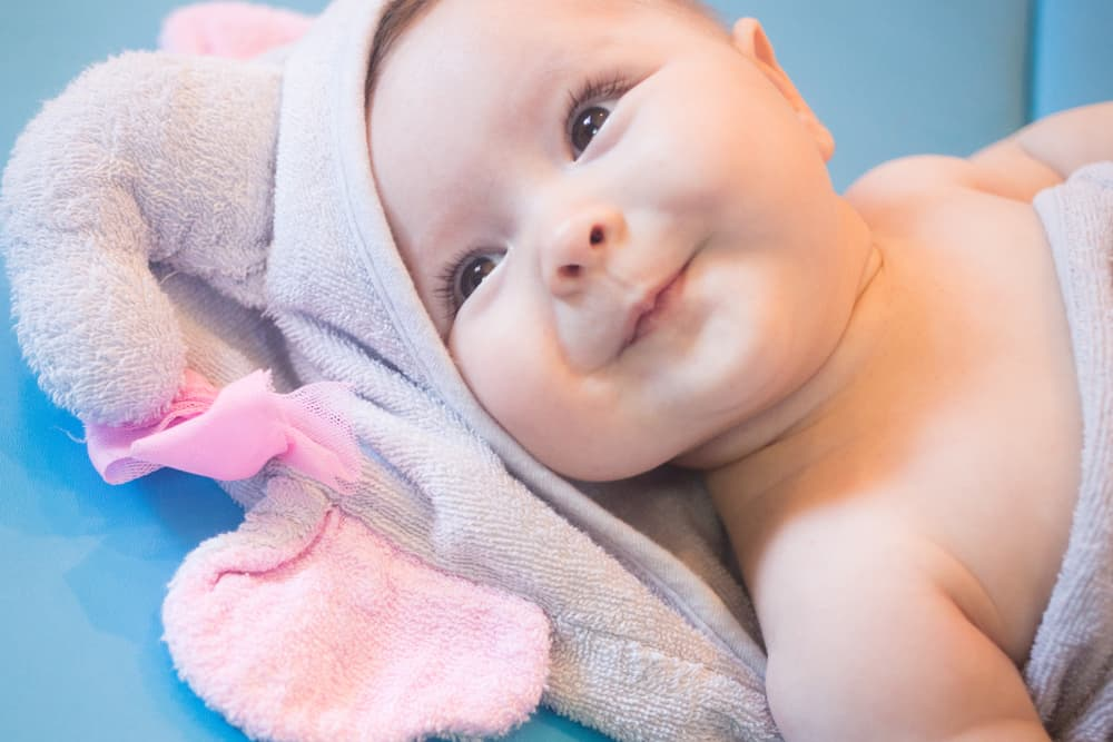 close up of smiling baby wrapped in a pink towel