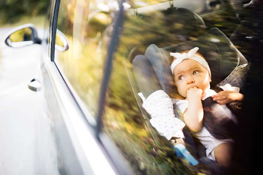 Baby fastened in car seat while looking out the window of the black car