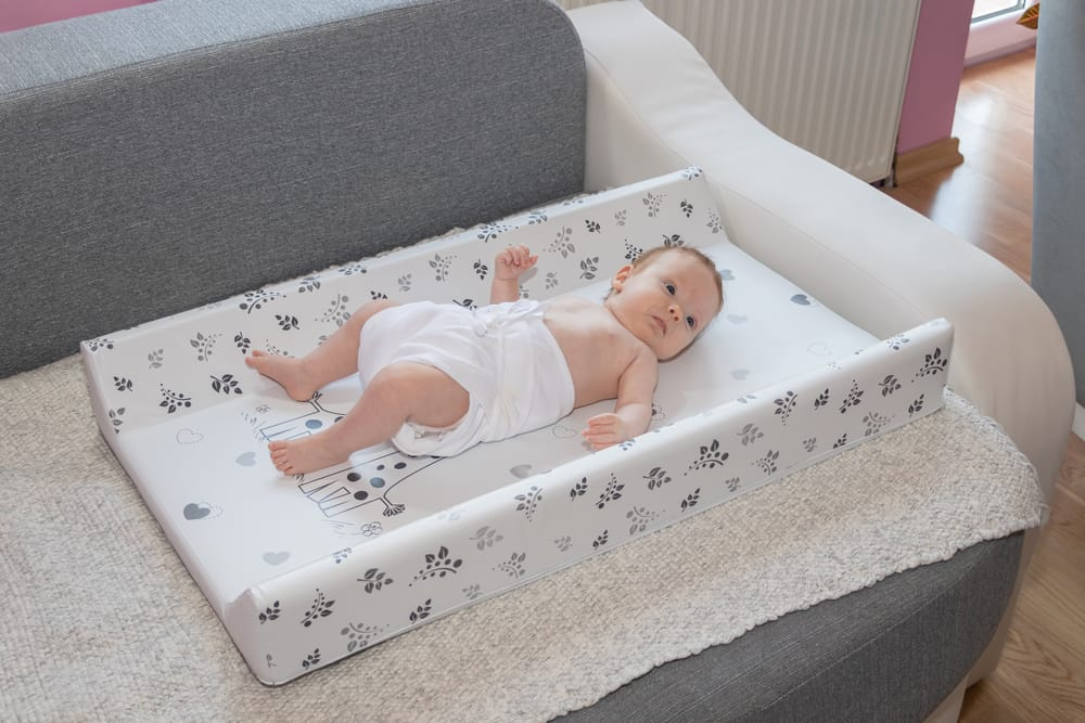 newborn baby laying down on changing pad