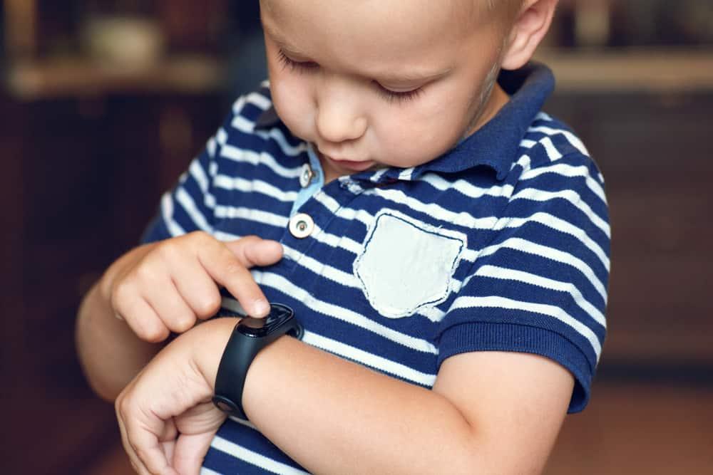 child checks fitness tracker watch