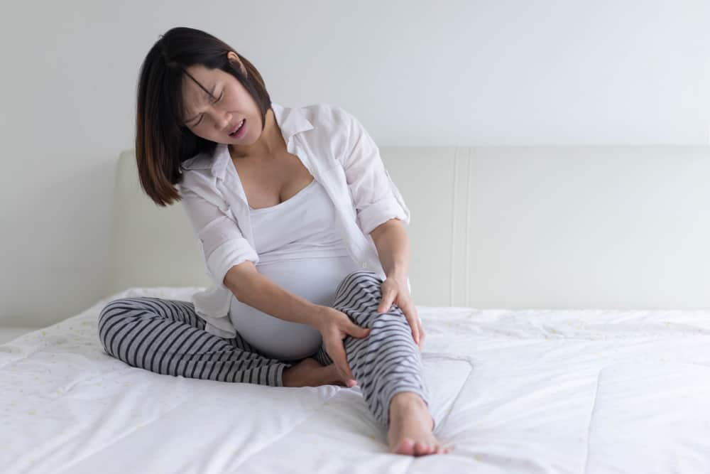 a pregnant woman suffering from leg cramps
