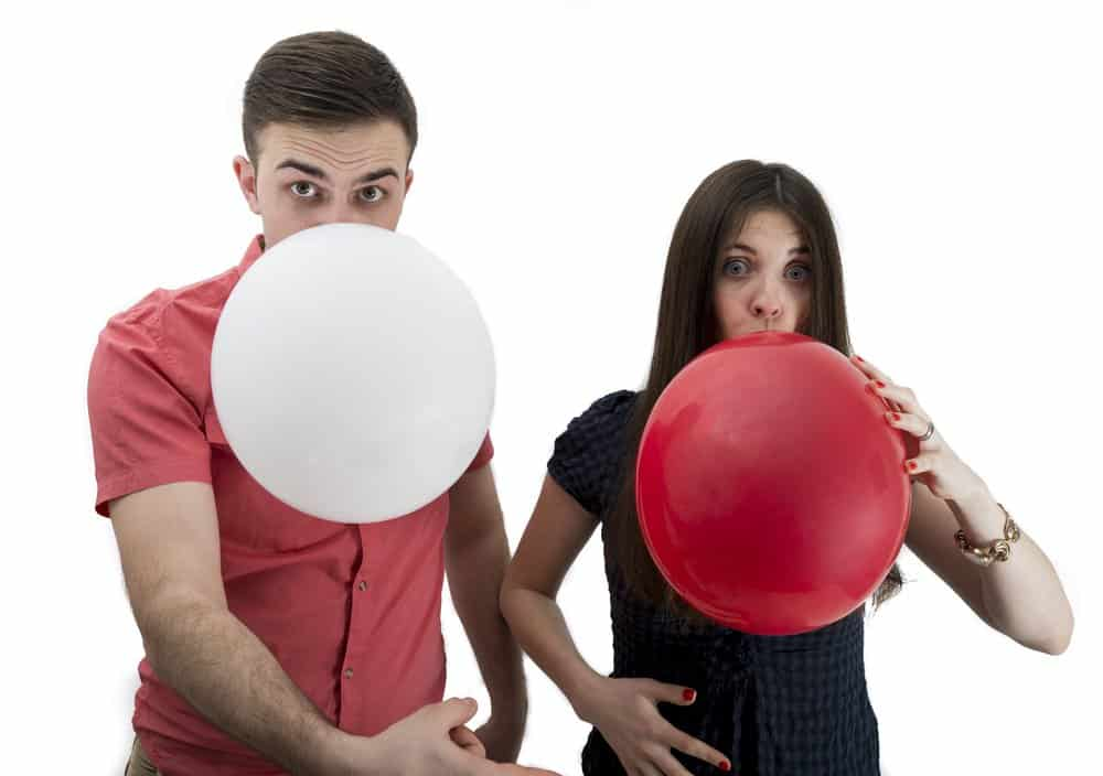 Couple blowing balloons for pregnancy announcement