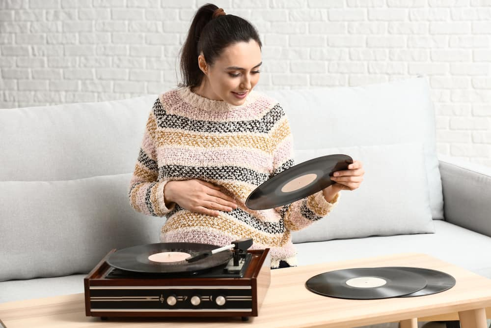 a pregnant woman chooses a record to listen to with her record player