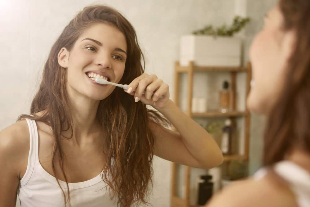 a woman looks in the mirror while brushing her teeth