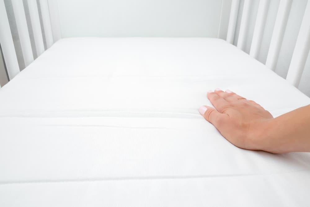 a woman's hand pressing down on a crib mattress