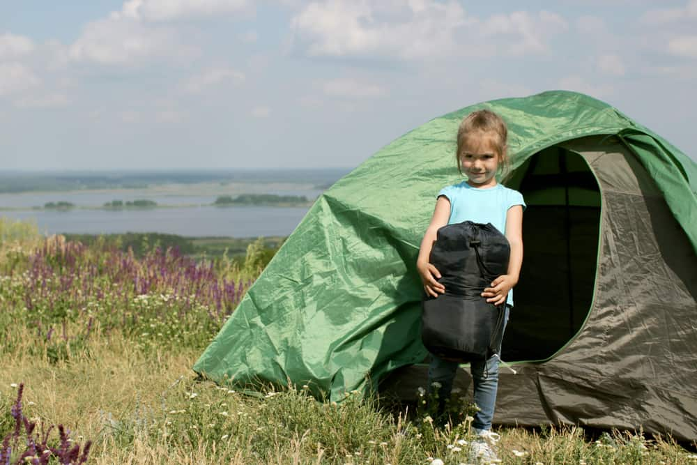 girl holding sleeping bag in front of tent