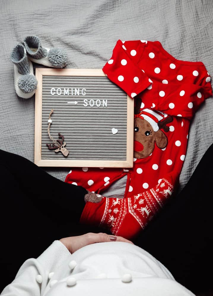 pregnancy announcement with Christmas onesie