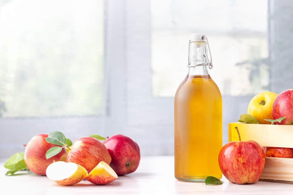 some apples and a bottle of apple cider vinegar