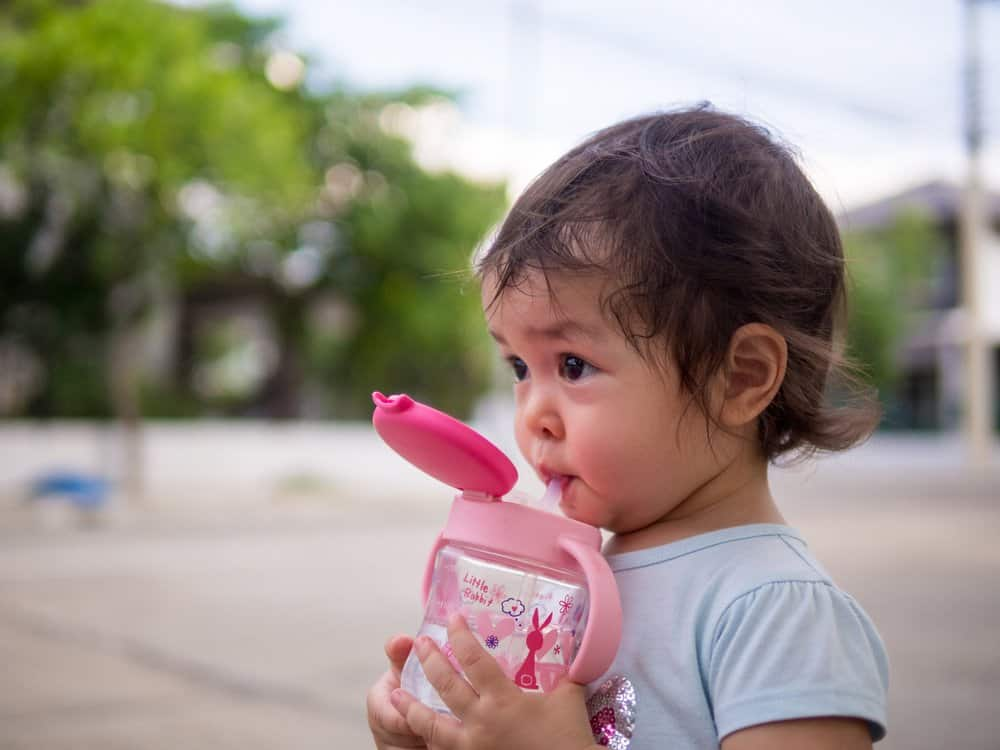 toddler drinking water outside