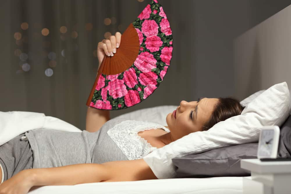 woman fanning herself in bed